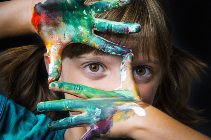 Photo of girl looking through painted hands at viewer.